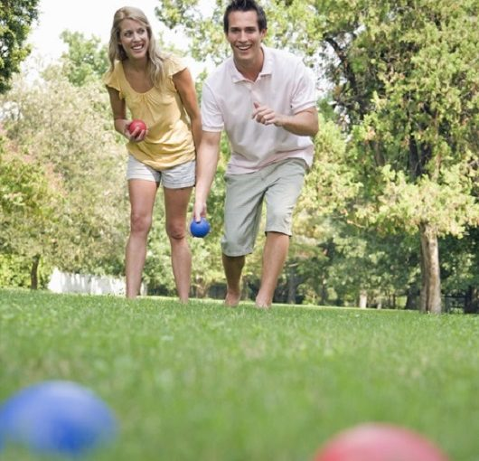 Man and Woman Outside Playing Bocce Ball