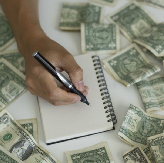 A person's hand writing on a notepad surrounded by $1 bills