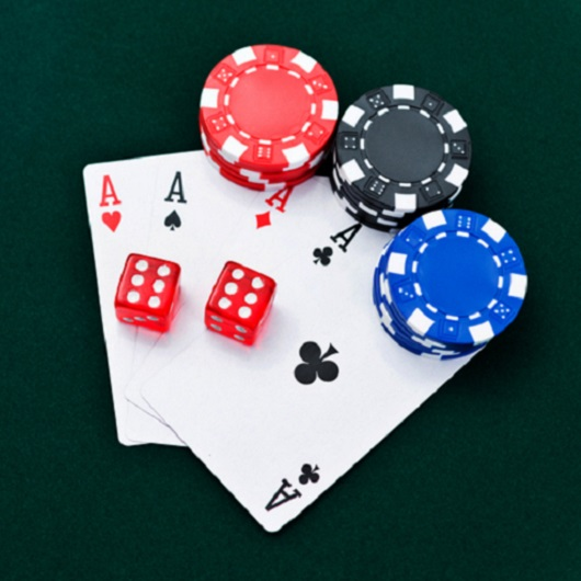 Four ace cards with dice and poker chips