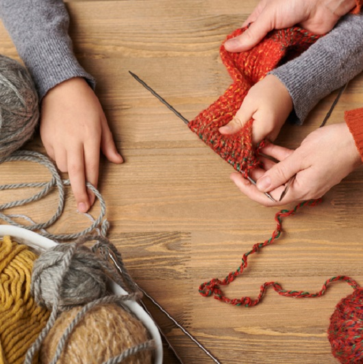 Child girl is learning to knit. Colorful wool yarns are on the wooden table. Ave Maria, Florida