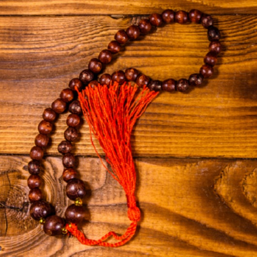 Brown rosary on the wooden table. Top view