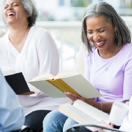 Two women reading books and laughing, in Ave Maria Florida
