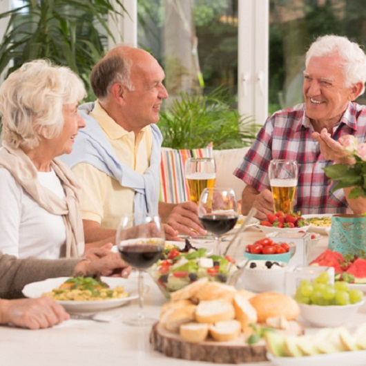 3 older people eating dinner and drinking alcoholic beverages in Del Webb Naples Ave Maria, Florida,