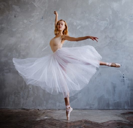 Young and slim ballet dancer is posing in stylish studio with big windows