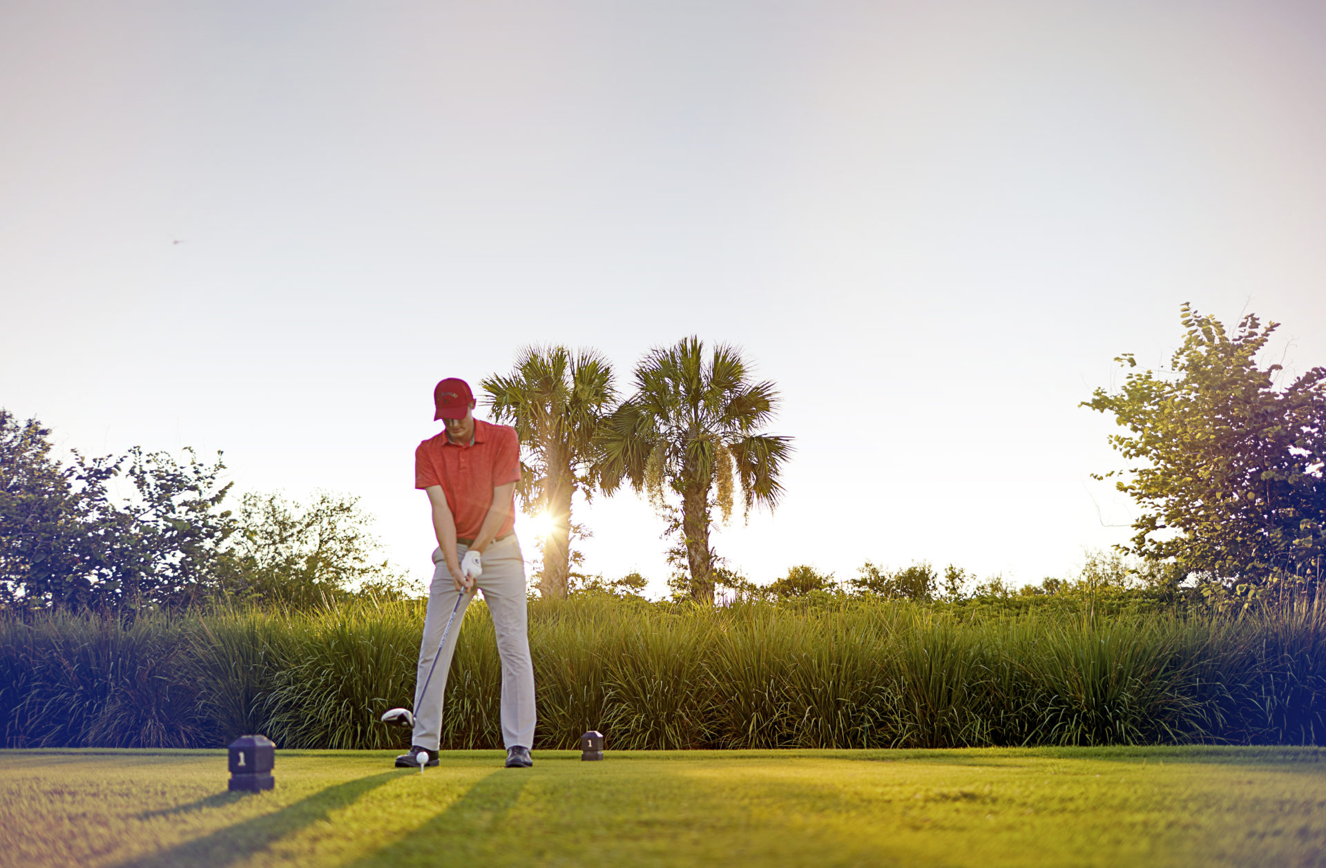 Golfer about to swing during sunset