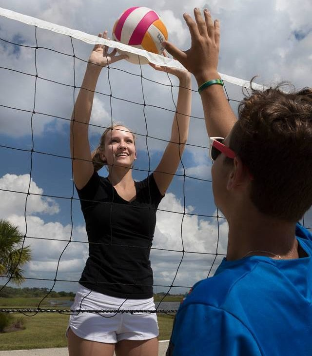 Girl playing Volleyball, hitting ball over net