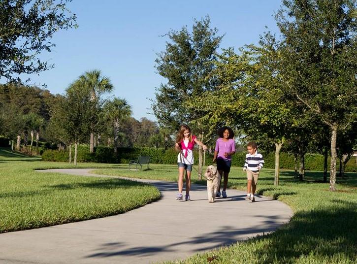 Children walking dog on sidewalk