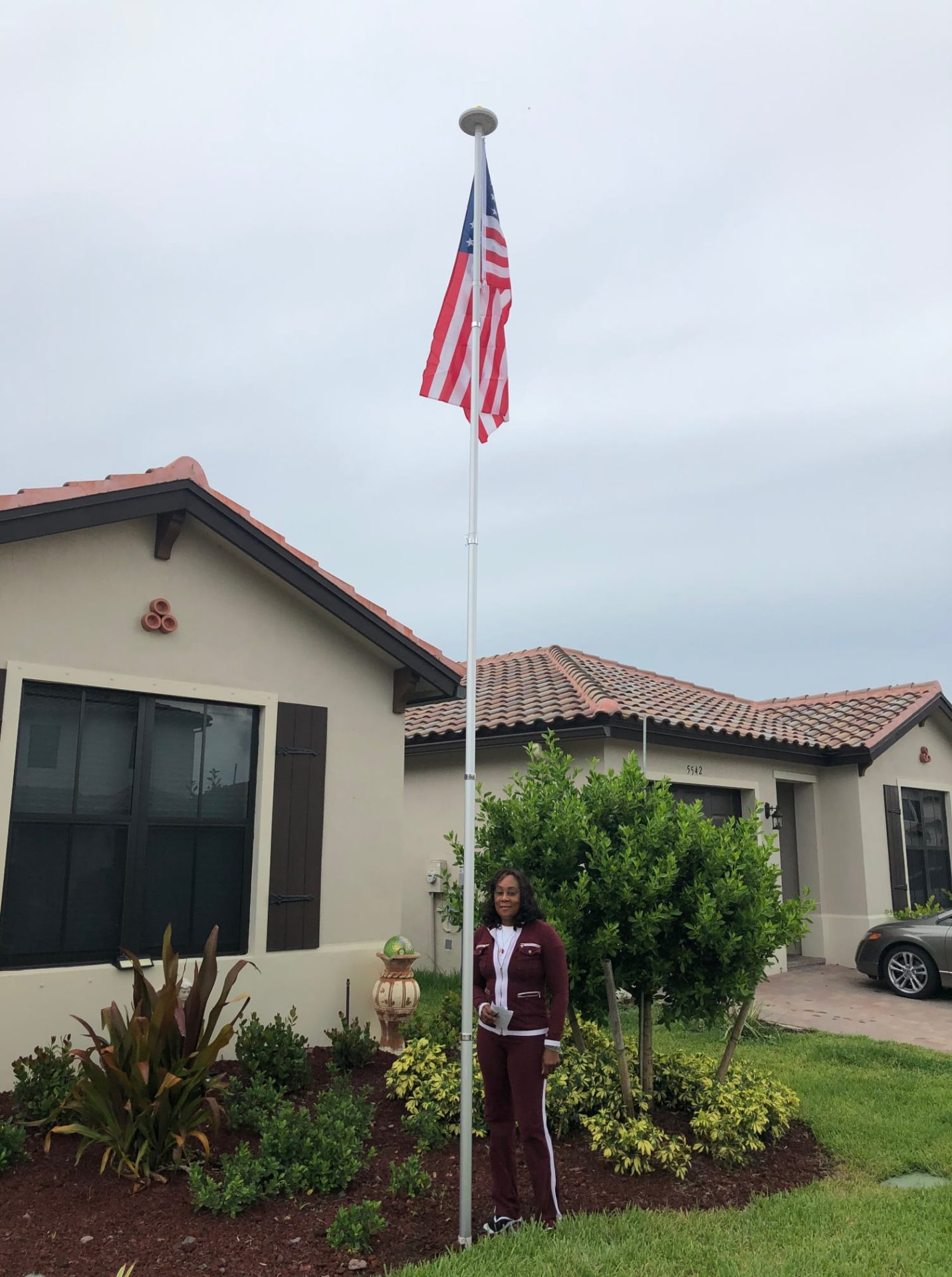 Woman standing outside home next to free-standing flagpole