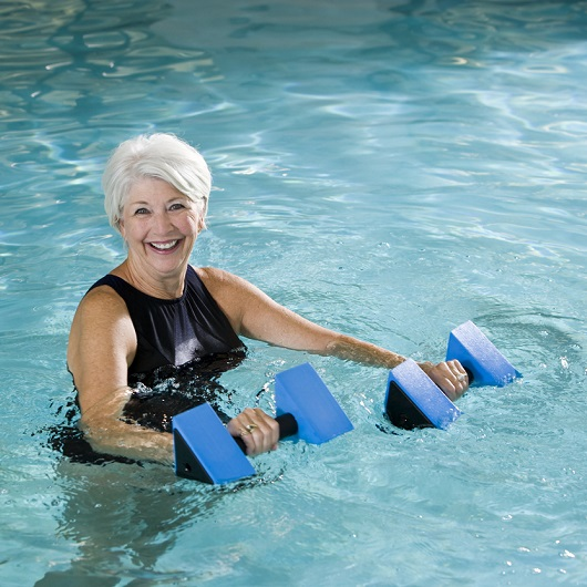 Active senior woman doing water aerobics
