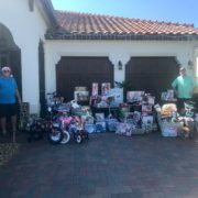 Two men standing next to hundreds of toys in Ave Maria, Florida