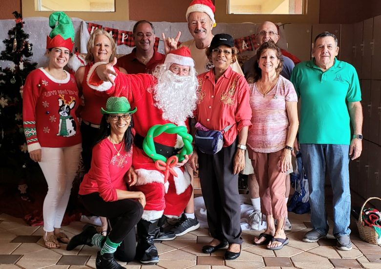 Group of people posing with Santa Claus