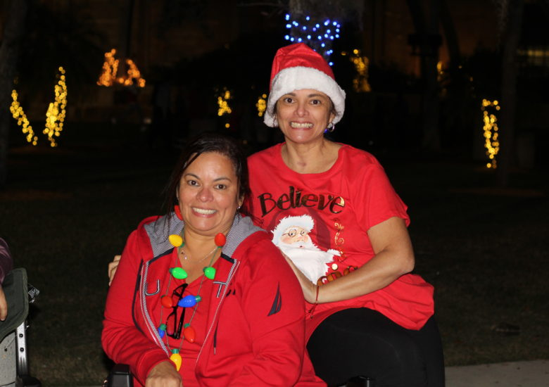 Two women in Christmas outfits smiling