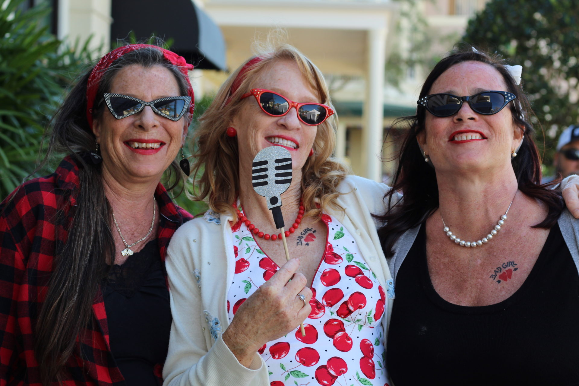 Three women smiling with microphone prop in hand