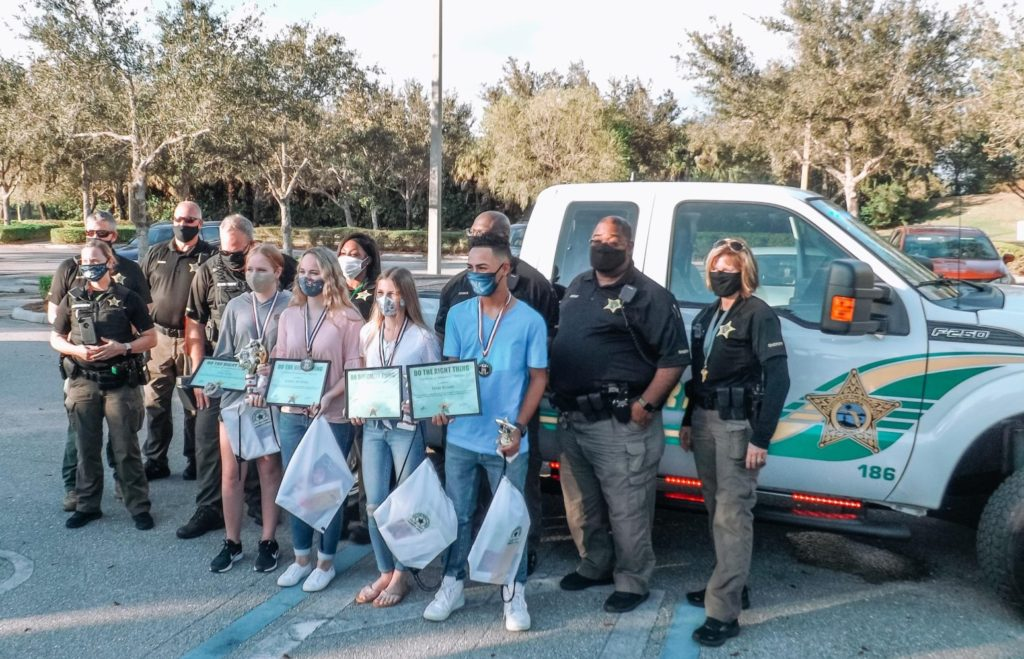 A group of students, Collier County deputies standing in front of truck with award