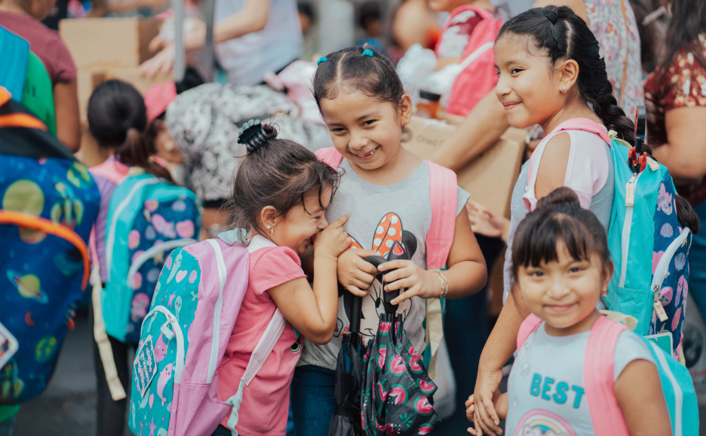 Four young girls smiling with backpacks on in crowd
