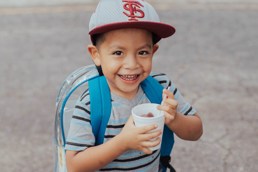 young boy smiling with cup in hand