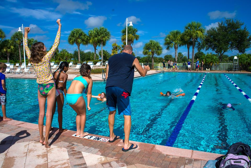 People standing by pool cheering on swimmer in Ave Maria Florida