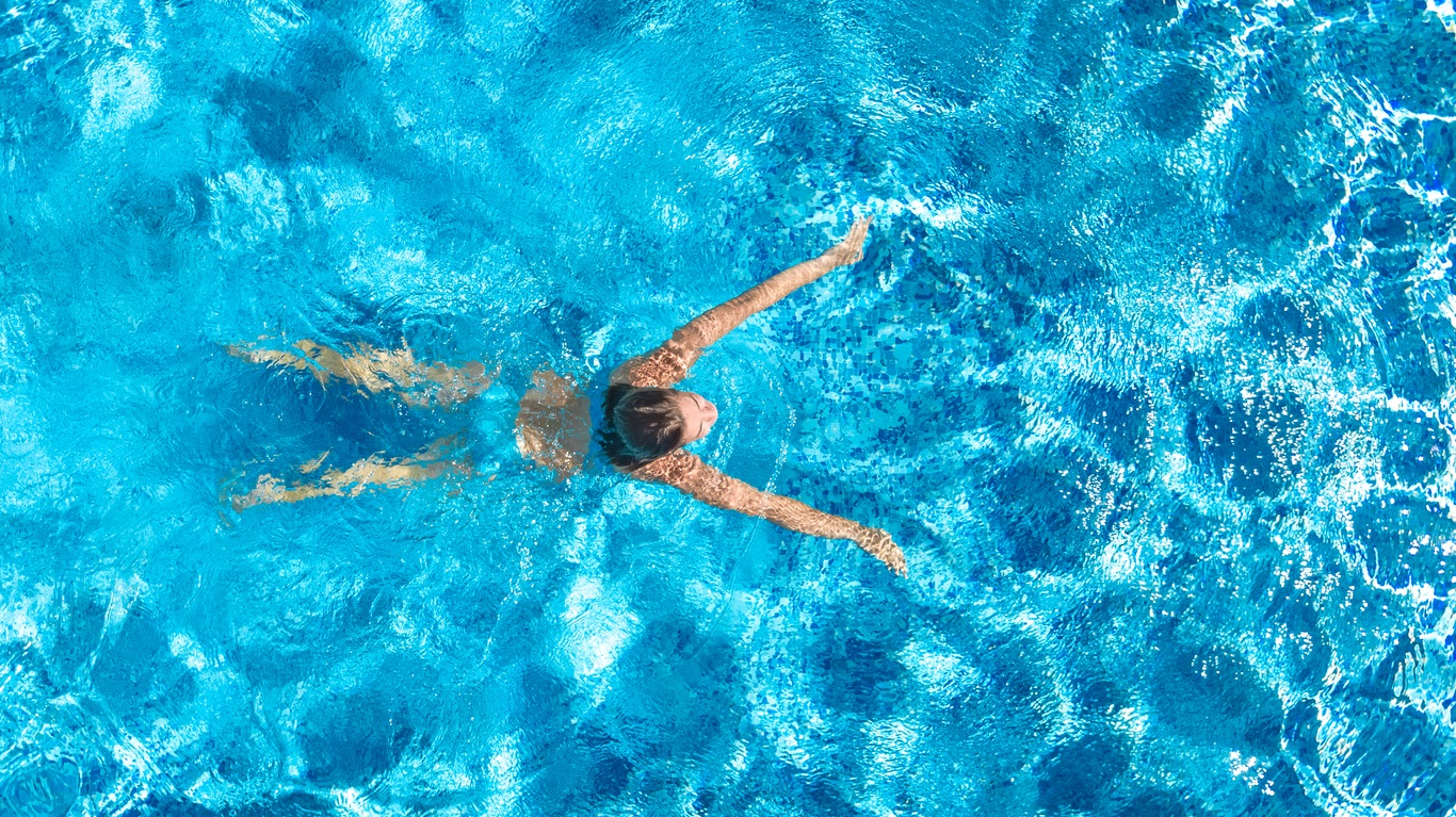 Active girl in swimming pool aerial drone view from above, young woman swims in blue water
