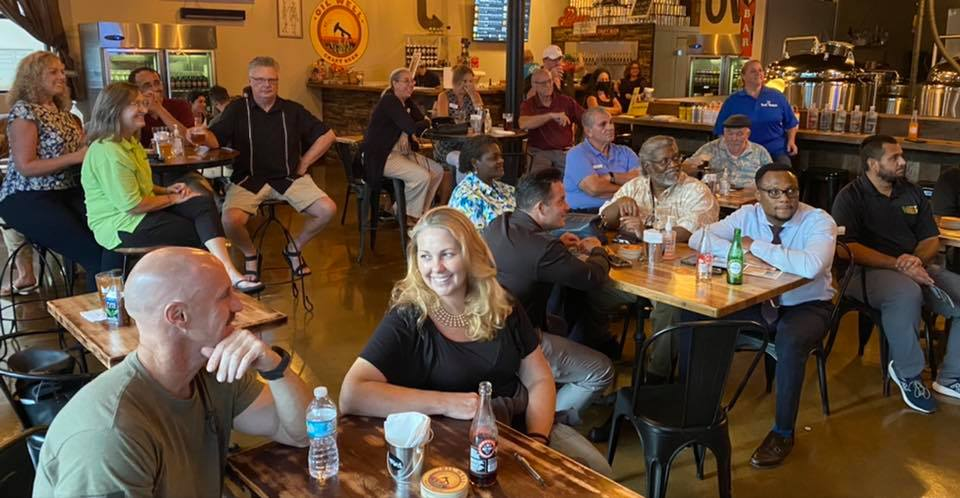 Group of people sitting, smiling inside bar in Ave Maria